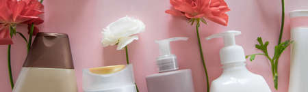 Top view of different hygienic/cosmetic products and flowers on fresh pink background. Wellness beauty treatment. Organic health care products