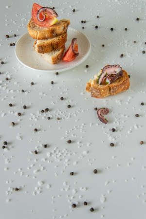 Top view of tasty Italian appetizers -  bruschetta with raw tomatoes and octopus tentacles, on slices of toasted baguette. White background with black pepper and sea salt