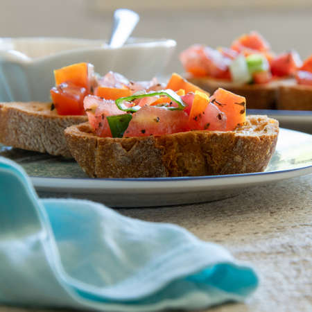 Close up view of tasty tomato Italian appetizers -  bruschetta, on slices of toasted baguette