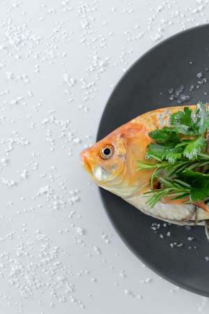 Cooking red  Carassius fish with fresh herbs. Healthy eating concept, space for text or menu