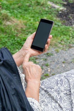 Close up view of modern senior lady hands with a smartphone Imagens