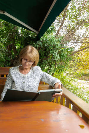 Attractive senior looking a menu in the outdoor restaurant. Healthy  and active lifestyle concept 스톡 콘텐츠