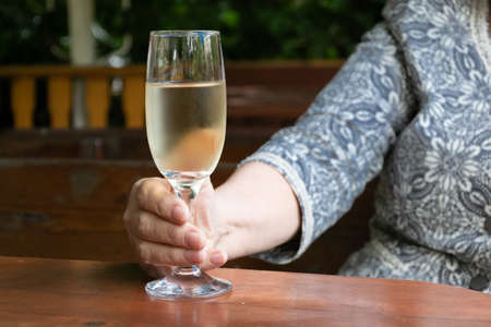 Close up view of modern senior lady hands holding a glass of white wine Stok Fotoğraf