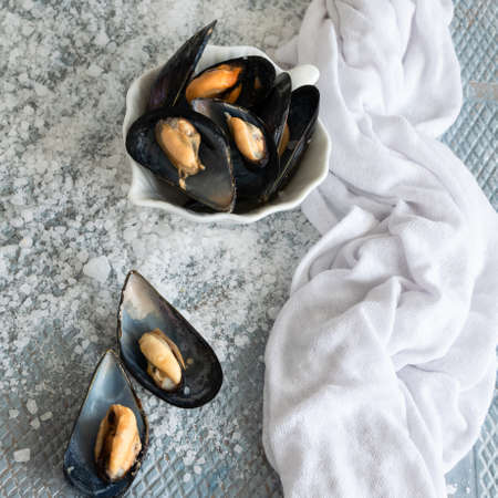 Cooked delicious black mussel, salty white background. Healthy eating concept, rich protein  food