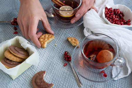 Refreshment time, Top view of woman hands holding a tasty homemade biscuits and pomegranate tea