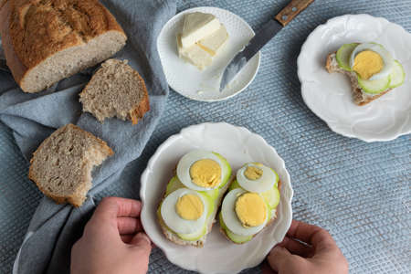 Top view of woman hands preparing healthy homemade sandwiches with vegetables and hard-boiled eggs