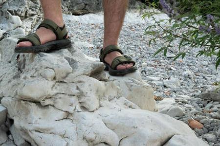 Ritagliare i piedi dell'uomo sulla roccia. Concetto di viaggiatore avventuroso
