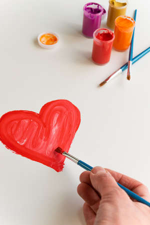 Top view of woman hand painting red heart on white background, artistic creative occupation, love concept
