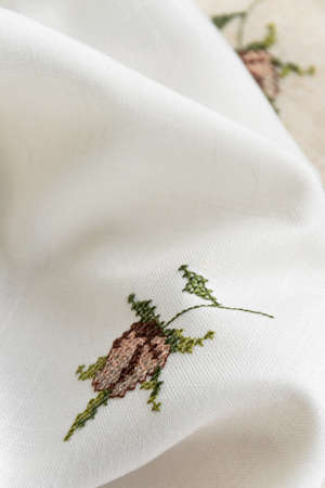 Close up view of the linen napkin with embroidery, piece of vintage calico