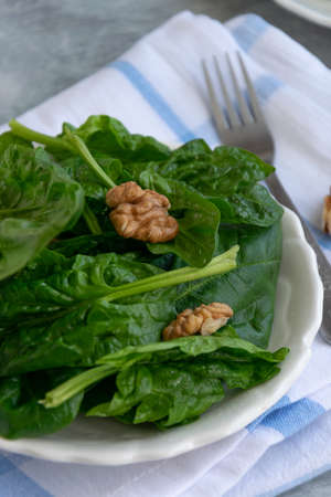 Close up view of raw spinach salad with walnuts