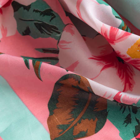 Fresh colorful folded cloth. Crop view of fashioned botanical fabric, pink and blue pastel colors