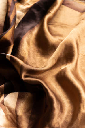 Folded silk golden tone cloth. Crop view of fashioned fabric piece