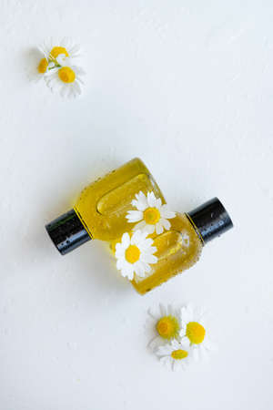 Essential oil with chamomile flower extract. Hygiene bath product. Wellness therapy regeneration