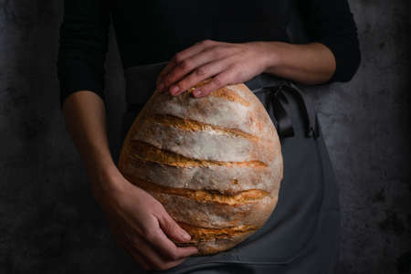 Baker woman holding a whole wheat round bread