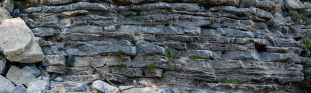 Natural wavy rocky formation along the river. Abstract rough natural background