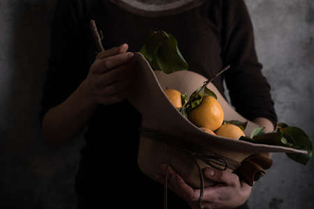 Close up view of woman holding an autumn hat with raw persimmons. Still life, fine art concept