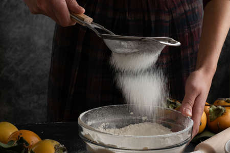 Woman sifting flour through sieve, preparing homemade sweet pie with raw persimmons