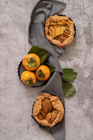 Ready to eat sweet pie with persimmons on gray cement background Stock Photo