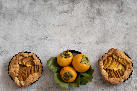 Ready to eat sweet pie with persimmons on gray cement background Reklamní fotografie