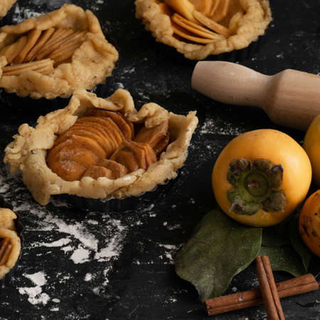 Preparing autumn sweet pie with raw persimmons