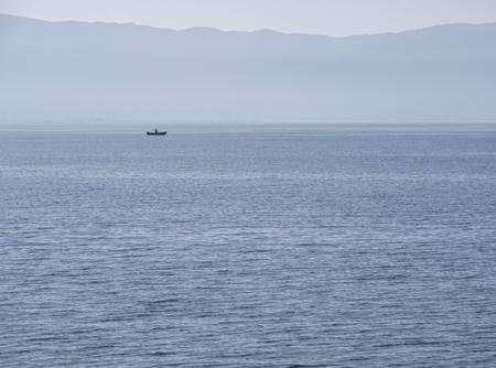 Blick auf das Meer bei Sonnenuntergang und den Fischer in der Ägäis auf der Insel Euböa, Griechenland