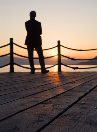 The figure of a man against the backdrop of the sunset in the Aegean Sea in Greece