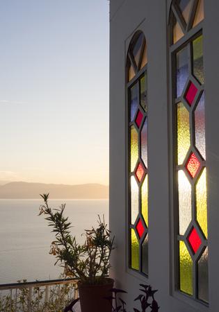Multicolored Windows the Greek Church overlooking the sea at sunset 版權商用圖片