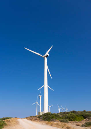 White wind turbines against the blue sky on the Greek island of Evia in Greece