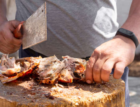 Man is chopping meat with an ax-knife traditional food - goat or lamb on a spit - for the Easter holiday on a wooden block on the Greek island Evia of Greece