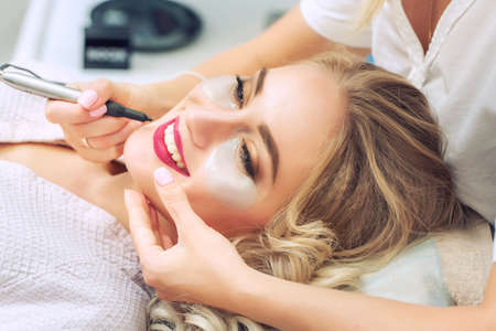 Cosmetologist applying permanent make-up on lips. Woman smiling at cosmetic salon