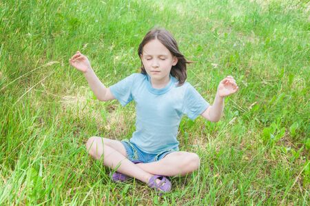 little one: summer girl child sitting on the grass meditating Stock Photo