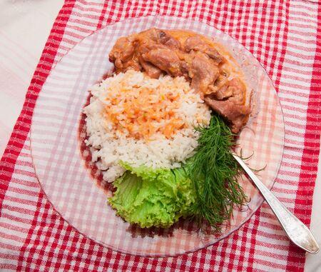 plato del buen comer: arroz con verduras y carne en una placa de vidrio en una mesa con una servilleta a cuadros