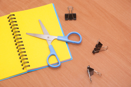 crayon  scissors: yellow notepad scissors and paper clips on a brown wooden surface Stock Photo