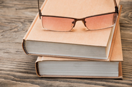 closed book: Two closed book and glasses on a brown wooden background
