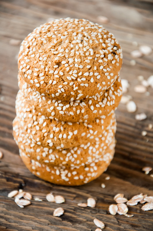 oatmeal: oatmeal cookies with sesame seeds are stacked on a brown wooden background