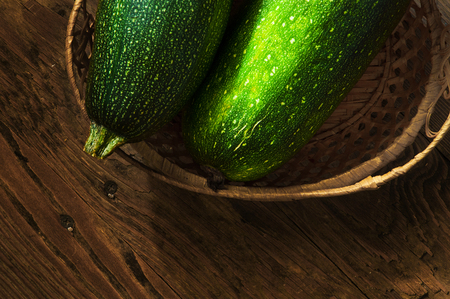 two zucchini in a wicker basket on a wooden table