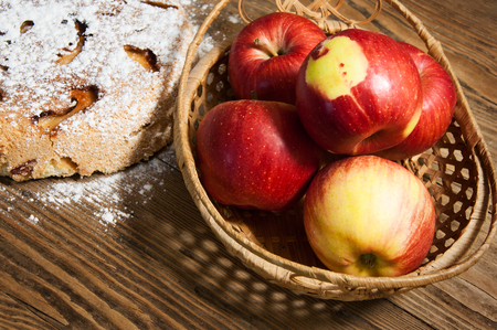 the sweet apple pie and fresh apples on a wooden table