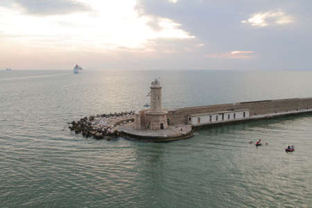 Lighthouse and breakwater in the port of Livorno; Italy photo