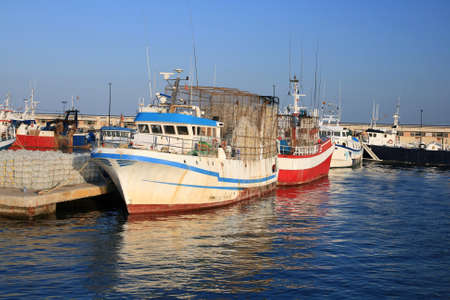 Fishing boats docked in port photo