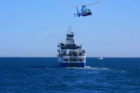 Helicopter and fishing boat sailing photo