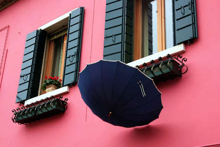 sestiere: Umbrella in the colored houses of Burano island