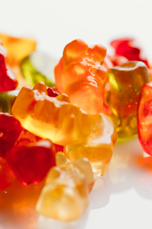 translucent red: gummi bears close-up on a light background.