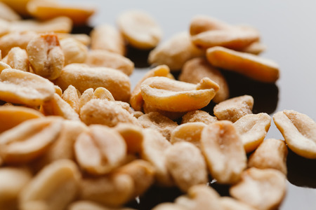 bunch of kernel peanuts on a dark background.