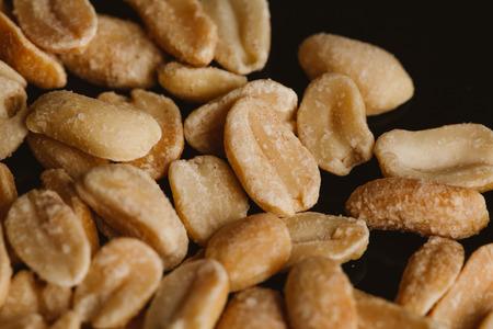 kernel: bunch of kernel peanuts on a dark background.