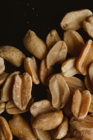 pine kernels: bunch of kernel peanuts on a dark background.