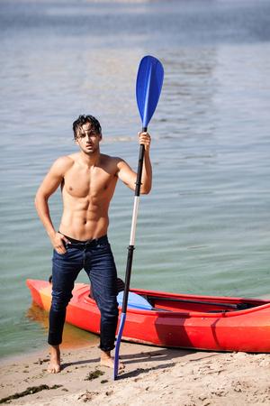 jonge man in een kano roeispanen roeien.