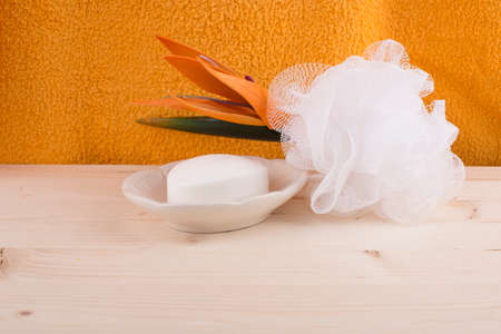 Soap-dish with soap,wisp of bast,orange flower on the wooden table photo