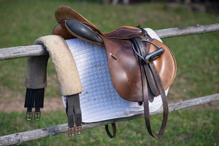 eventing: Close-up of a horse saddle on top of a wooden fence of the paddock