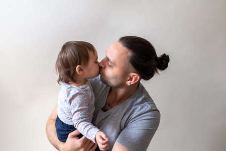 Father kiss his lovely and cute little daughter on white background. Father's day conception