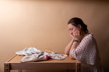 Tired young mother in white blouse sitting at a table with diapers after a working day